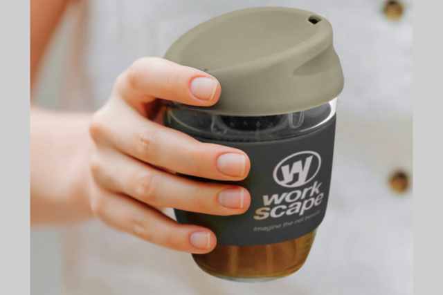 Woman holding promotional reusable coffee cup