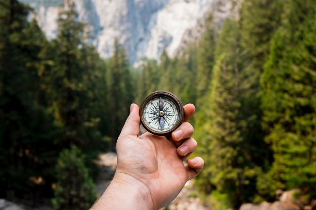 Man holding compass in woods