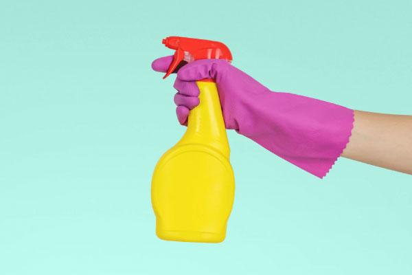 Purple glove holding yellow spray bottle