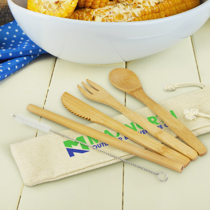 Bamboo cutlery set on table next to bowl of corn