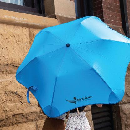 Woman holding blue BLUNT promotional umbrella