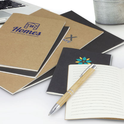 Assortment of promotional notebooks on desk with pen