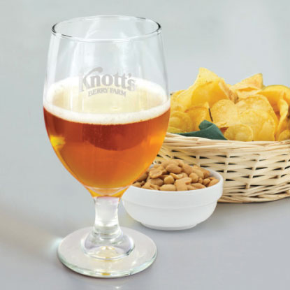 Promotional beer glass next to chips and nuts