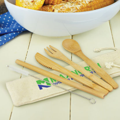 Bamboo cutlery set on wooden table next to corn